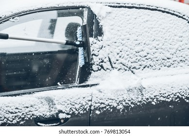 cleaning car from a snow in winter day