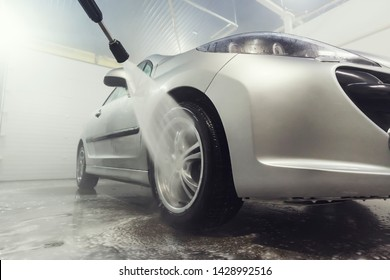 Cleaning Car Using High Pressure Water. Man washing his car under high pressure water in service. Self-cleaning stylish car in the garage. Wash kolesnogo drive.