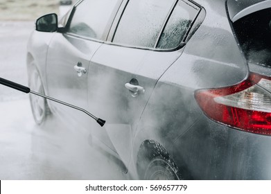 Cleaning Car Using High Pressure Water. Soft focus.