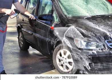 Cleaning Car Using High Pressure Water. Man washing his car under high pressure water in service