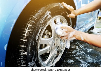 Cleaning the car wheels with microfiber cloth While washing the car