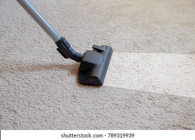 Cleaning the carpet using a vacuum cleaner.