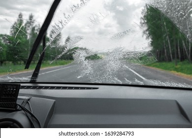 Cleaning the car's windshield with a windscreen wiper. Inside view
