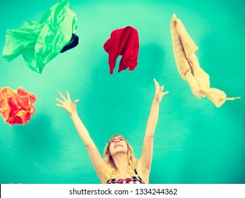 Cleaning in the closet, fashion, happiness concept. Woman throwing up lot of clothes. Clothing flying all over the place