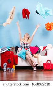 Cleaning in the closet, packing for travel, fashion, happiness concept. Woman sitting on sofa throwing up lot of clothes. Clothing flying all over the place