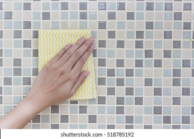 Cleaning colorful wall by woman hand