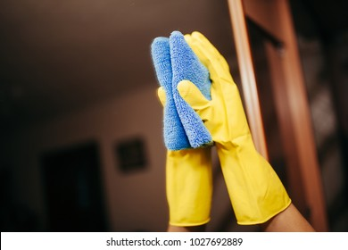 cleaning company. Employee hand in rubber protective glove with micro fiber cloth washing a mirror