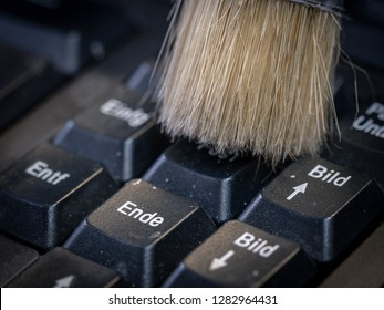 Cleaning the computer keyboard with a brush