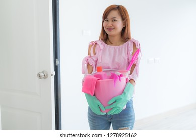 Cleaning concept. Asian woman with bucket of cleaning supplies