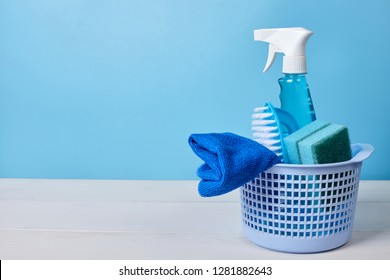 Cleaning concept. Bucket with brush, house-cleaning spray and sponges. Blue background with copy space.