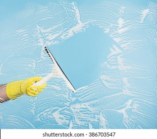 Cleaning concept - hand cleaning glass window pane with detergent and rubber aluminum wiper