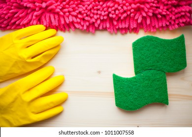Cleaning Concept. Set of yellow, green, blue, red and pink cleaning tools: rags, sponges, brushes, dishwashing liquid, hands in rubber gloves on the light wooden background, top view, flat lay