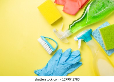 Cleaning concept - cleaning supplies, gloves, bottles on pastel yellow background, copy space