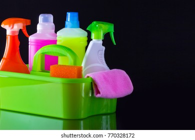 Cleaning concept with supplies on black background.
