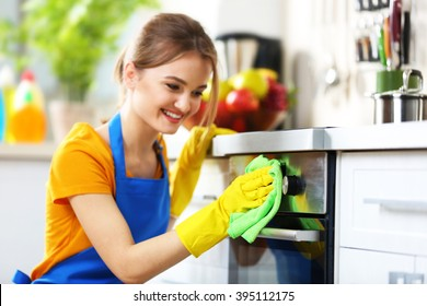 Cleaning concept. Woman washes an oven, close up