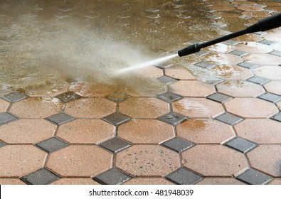 Cleaning concrete block floor by high pressure water jet.