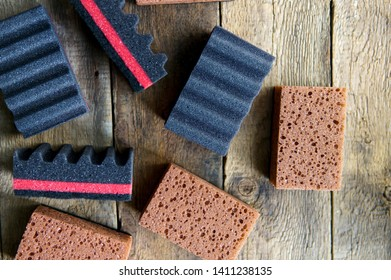 Cleaning Day Concept Sponges, black and brown cleaning sponges over wooden background