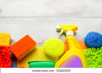 Cleaning day concept with supplies over wooden background