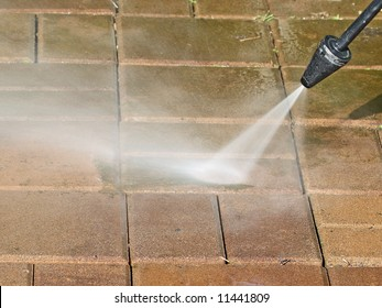 cleaning dirty patio with pressure washer