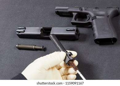 Cleaning a disassembled handgun with a wire brush