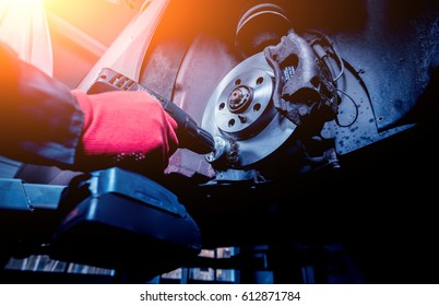 Cleaning disc brake on car, in process of new tire replacement. Car brake repairing in garage