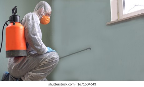 Cleaning and Disinfection at town complex amid the coronavirus epidemic. Professional teams for disinfection efforts. Infection prevention and control of epidemic. Protective suit and mask
