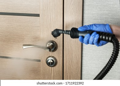 cleaning  door handle with steam generator, hand in blue glove holds steam genetator and hose with brush, which produces steam for disinfection from microbes, dirt and viruses, home cleaning concept
