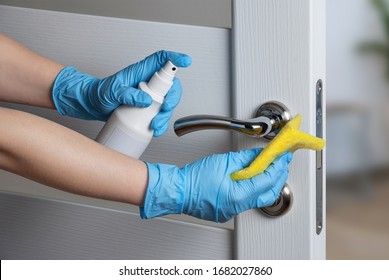 Cleaning door handles with an antiseptic during a viral epidemic - Shutterstock ID 1682027860