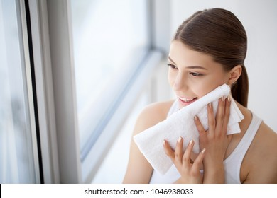 Cleaning Face Skin. Closeup Portrait Of Beautiful Happy Smiling Girl Holding Clean White Towel Near Facial Skin After Washing Face. High Resolution