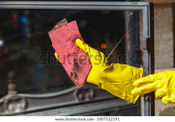 Cleaning the fireplace. Hands in yellow rubber gloves wash a pink rag with a glass fireplace door