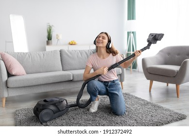 Cleaning is fun. Cheerful young housewife listening to music in headphones while vacuuming her apartment, using hoover as guitar, indoors. Playful millennial lady enjoying domestic chores
