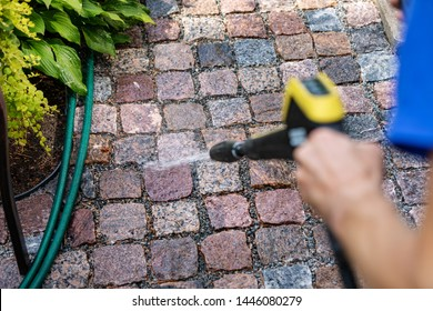 cleaning the garden cobblestone pathway with a high pressure washer