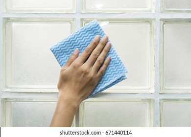 Cleaning glass block by woman hand