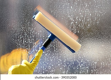 Cleaning a glass with a squeegee, close up