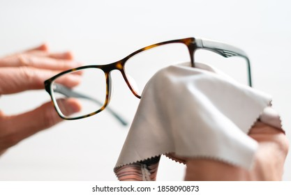 Cleaning glasses. A man wipes his glasses with a cloth. Selective focus. - Shutterstock ID 1858090873