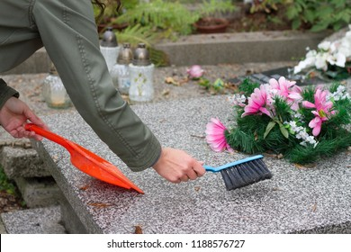 Cleaning grave on cemetery before All Saints' Day