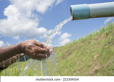 cleaning hands under an outdoor pipe pouring water. sky and cloud background