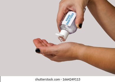 Cleaning hands with waterless, alcohol-based hand sanitizer antiseptic gel. Female holds bottle for handrubs & pours liquid used as hand disinfectant.