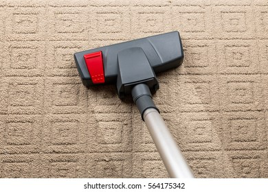 Cleaning home carpet from dirt and dust with a vacuum cleaner,