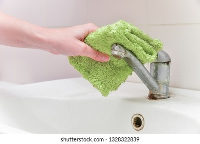 Cleaning the house. Cleaning chrome-plated metal surfaces. Cleaning the bathroom. Cleaning of water tap an calcified in domestic bathroom with small brush.