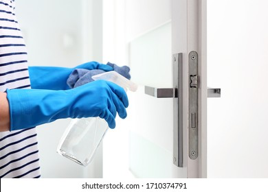 Cleaning the house, cleaning door handles. Prevention and prevention of infection. The woman cleans the apartment.