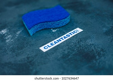 Cleaning house or office concept. Cleaning blue brush, cleantastic inscription on a dark concrete background. Top view, closeup