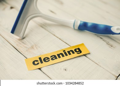 Cleaning house or office concept. Blue glass cleaning brush and Cleaning inscription on a white wooden background. Top view, closeup