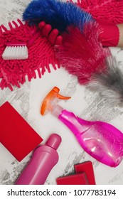 Cleaning house or office concept. Hands in red rubber gloves holding dust brush, red and pink cleaning supplies, white stone background, top view