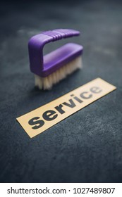 Cleaning house or office concept. Purple cleaning brush, SERVICE inscription on a dark concrete background. Top view, closeup