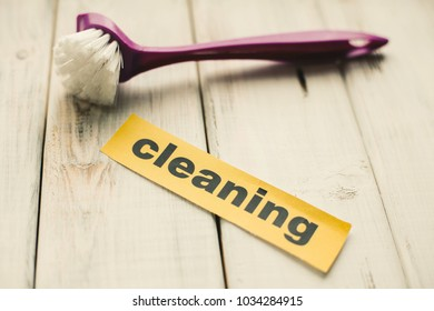 Cleaning house or office concept. Purple cleaning brush and Cleaning inscription on a white wooden background. Top view, closeup