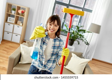 cleaning, housework and housekeeping concept - happy asian woman or housewife in gloves with window cleaner and sponge mop at home