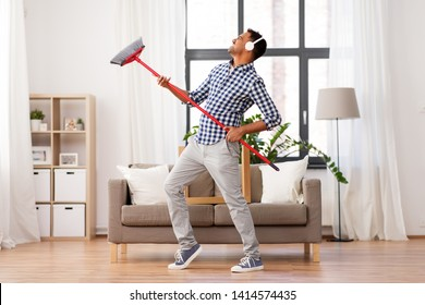cleaning, housework and housekeeping concept - indian man in headphones with broom sweeping and having fun at home