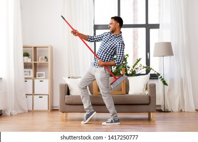 cleaning, housework and housekeeping concept - indian man with broom sweeping floor and having fun at home