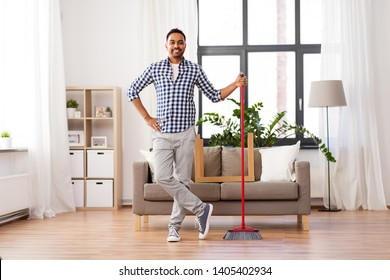 cleaning, housework and housekeeping concept - smiling indian man with broom at home
